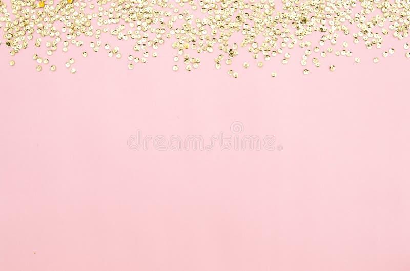 Guld- paljetter på en rosa färgpappersbakgrund Dekorativ tillbehör för att sy och broderi Cirkelform som skiner arkivbild
