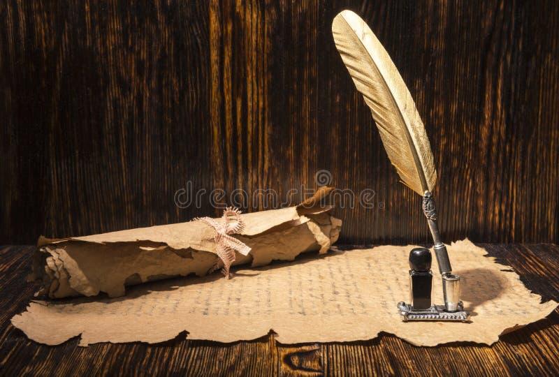 Guld- penna och forntida manuskript arkivfoto