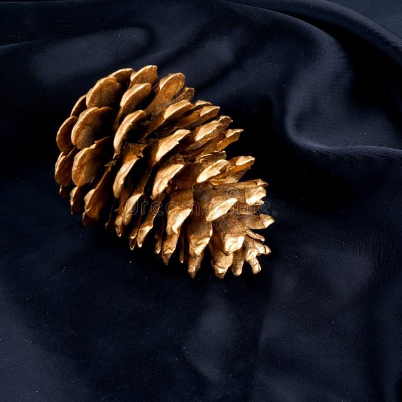 Guld- pinecone som isoleras på svart silke Lyxig bakgrund royaltyfri foto
