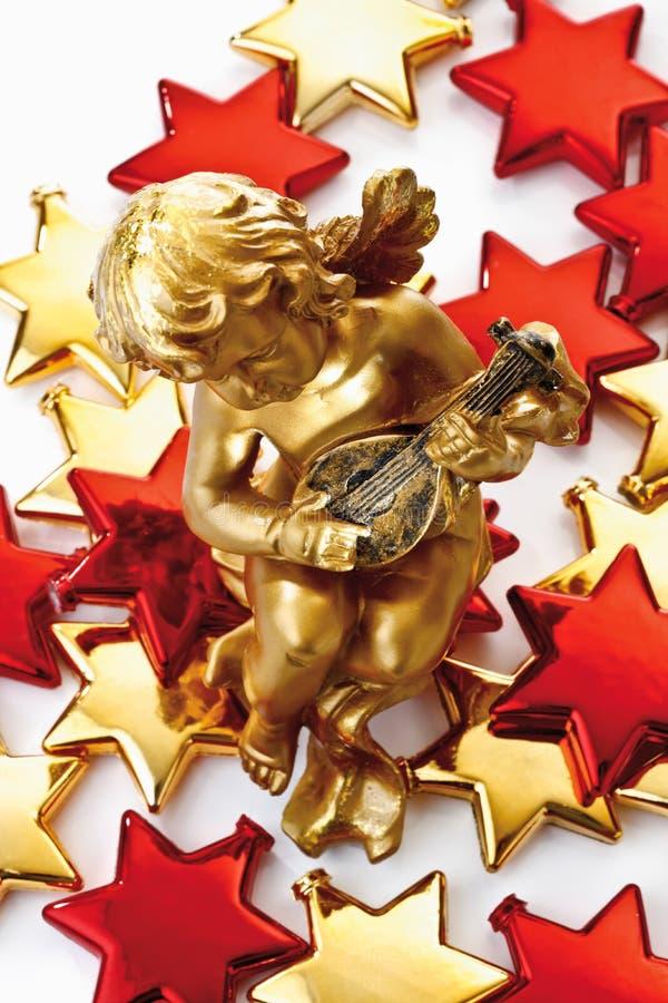 Guld- putto på guld- och röda stjärnor royaltyfri bild