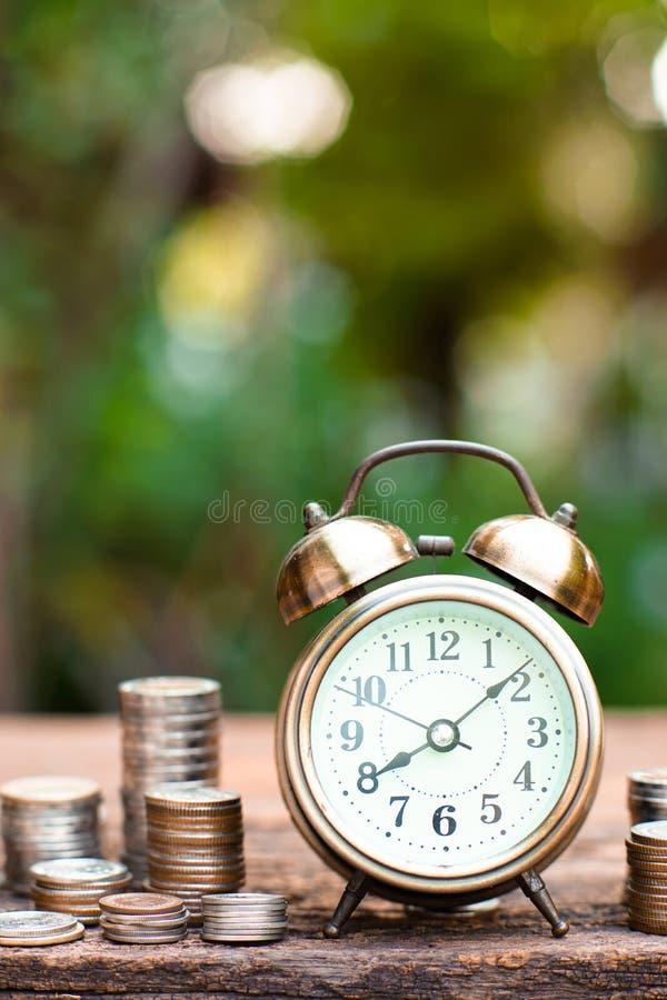 Guld- ringklocka för tappning med buntar av myntet Time och pengar för finansiellt begrepp arkivbilder