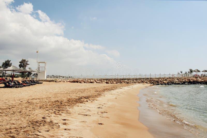 Guld- sandig strand med solsängar, azurt havsvatten och den vita vågbrytaren i solig dag Härligt medelhavs- kustlinjelandskap arkivbilder