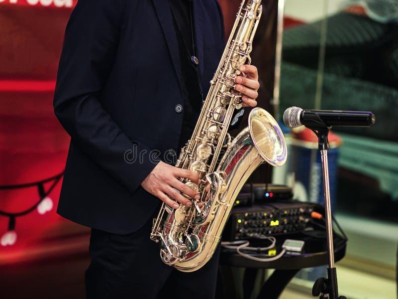 Guld- saxofon med fläckar på den i manhänder i den röda backgren royaltyfri foto