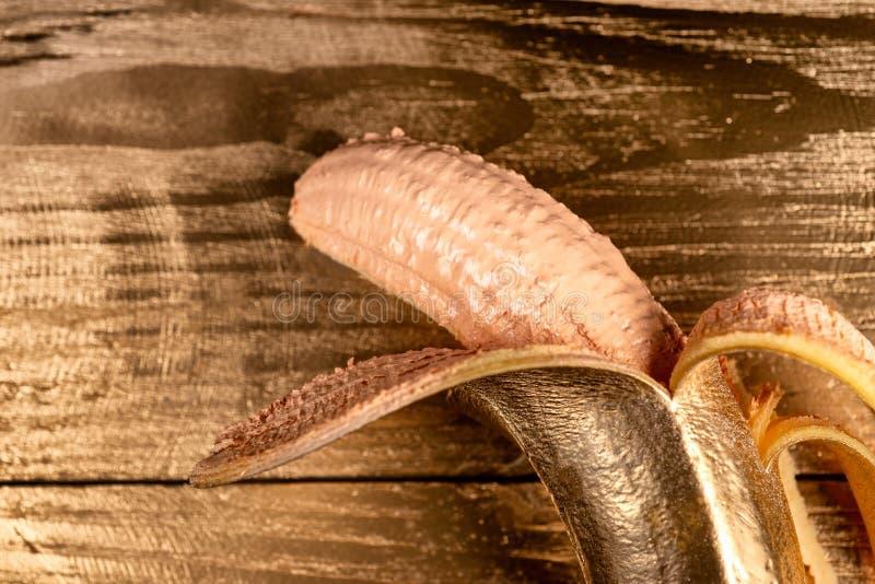 Guld skalad banan på träbakgrund arkivbild