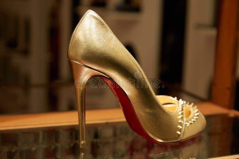 Guld- skor Christian Louboutin f?r h?g h?l med dubbar och r?tt endast i lyxigt lager f?r mode arkivfoton