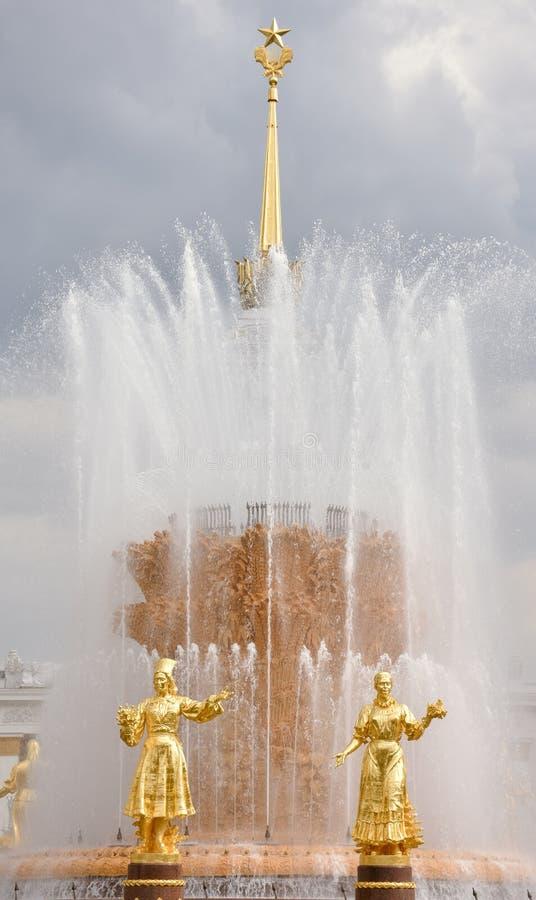 Guld- skulpturer av springbrunnkamratskapet av folk royaltyfri bild