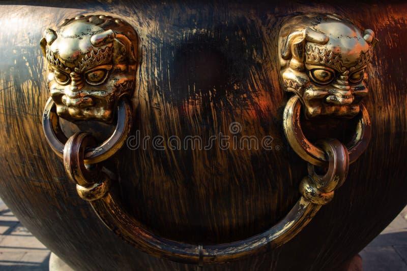 Guld- skyttel med handtaget och två buddistgudframsidor som göras av bronsmetall royaltyfria bilder