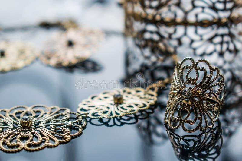 Guld- smycken är gula och olika skuggor Smycken från metalllegeringen med openwork modeller på den reflekterande yttersidan fotografering för bildbyråer
