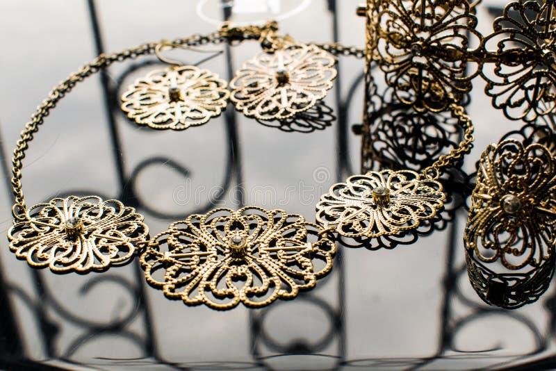 Guld- smycken är gula och olika skuggor Smycken från metalllegeringen med openwork modeller på den reflekterande yttersidan arkivbilder