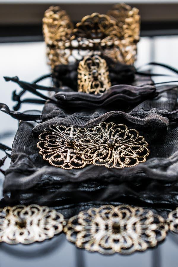 Guld- smycken är gula och olika skuggor Smycken från metalllegeringen med openwork modeller på den reflekterande yttersidan arkivfoton
