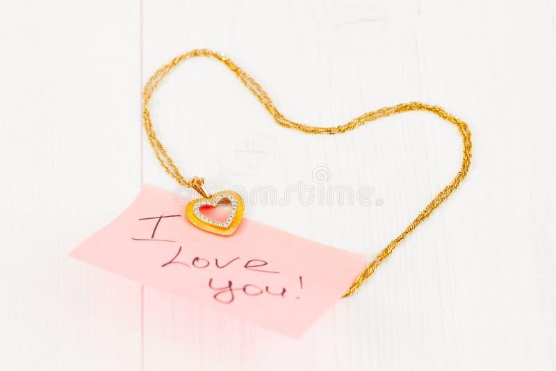 Guld- smycken i formen av en hjärta royaltyfria foton