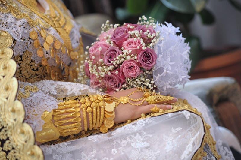 Guld- smycken och rosor på händerna fotografering för bildbyråer