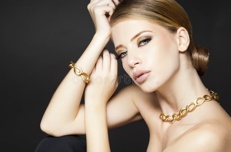 Guld- smycken på härligt posera för kvinnamodell som är glamoröst royaltyfri foto