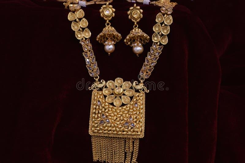 Guld- smycken - utsmyckat märkes- par av örhängen med uppsättningen för kedjehängehals för kvinnamode arkivfoto