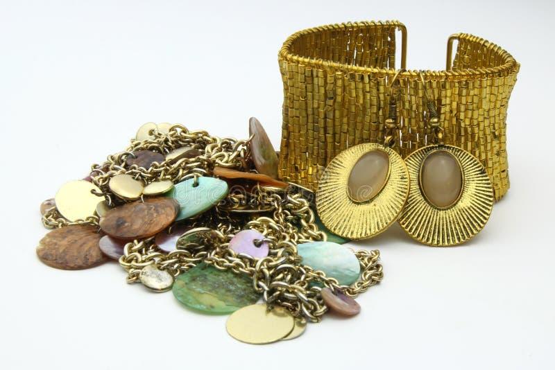 Guld- smyckenförtjänster, bracelete och halsband royaltyfria bilder