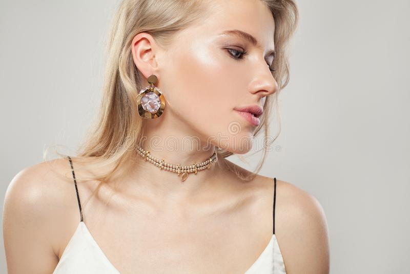 Guld- smyckenmodell Härlig blond kvinna med guld- örhängen och halsbandet på vit bakgrund Perfekt kvinnlig profil arkivbilder