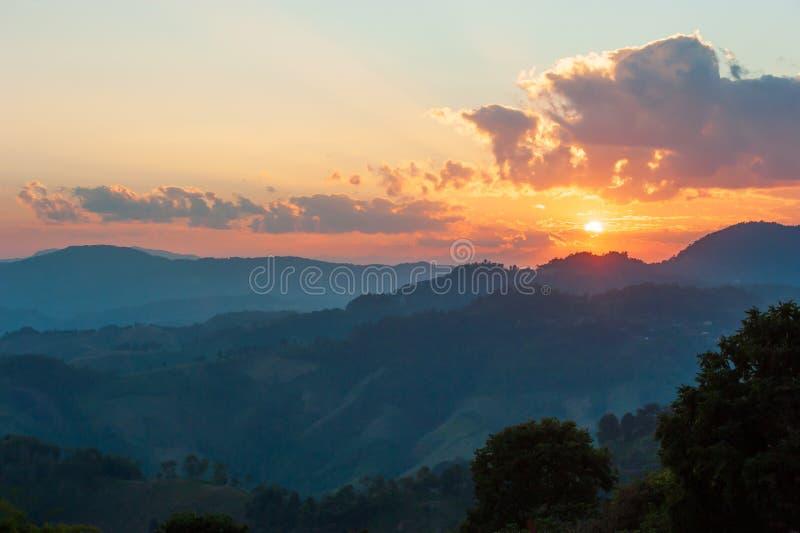 Guld- solinställning över bergöverkanten av Doi Mae Salong på denMyanmar gränsen Fantastiska moln och solnedgånghimmel Mae Fa royaltyfri foto