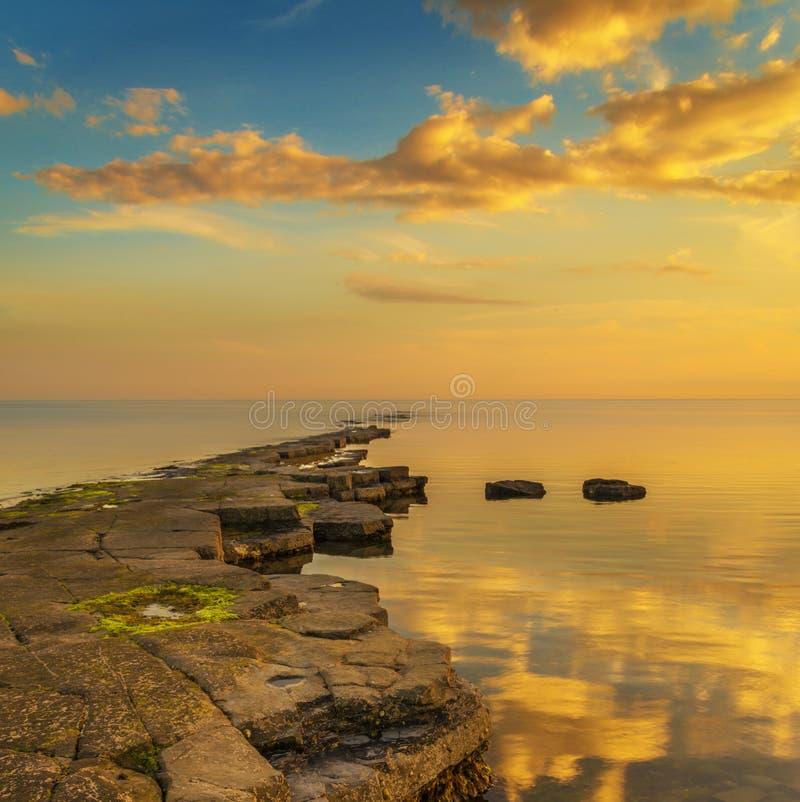 Guld- solljus exponerar en avsats på Kimmeridge royaltyfria bilder