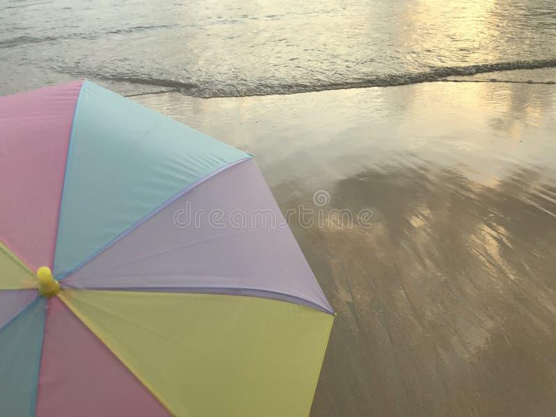 Guld- solljussken på stranden och det mångfärgade pastellfärgade paraplyet royaltyfri bild