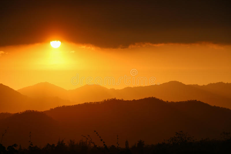 Guld- solnedgång över berget och skog arkivfoton