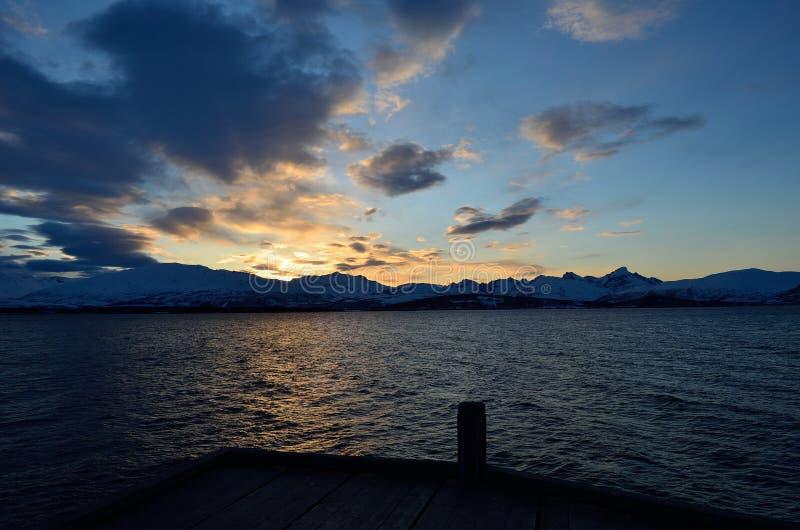 Guld- solnedgång över det snöig berget med reflexion på fjorden arkivfoton