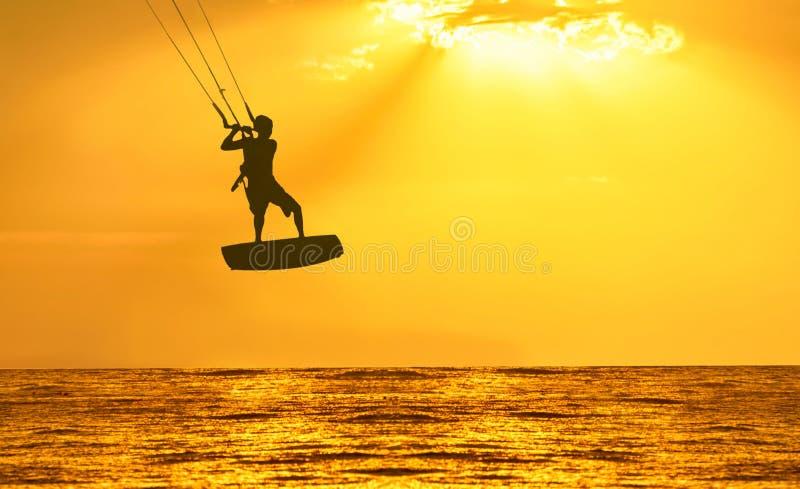 Guld- solnedgång över havet med männen som kiting konturn royaltyfria foton