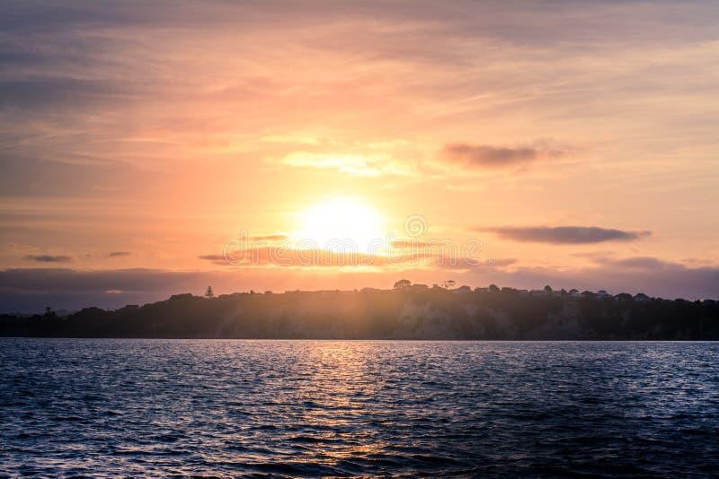 Guld- solnedgång över lugna fjärdvatten med den bergiga kusten på avståndet royaltyfri foto