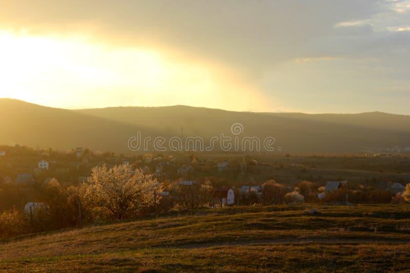 Guld- solnedgång- och bergdal, en by i bergen i vår arkivbild