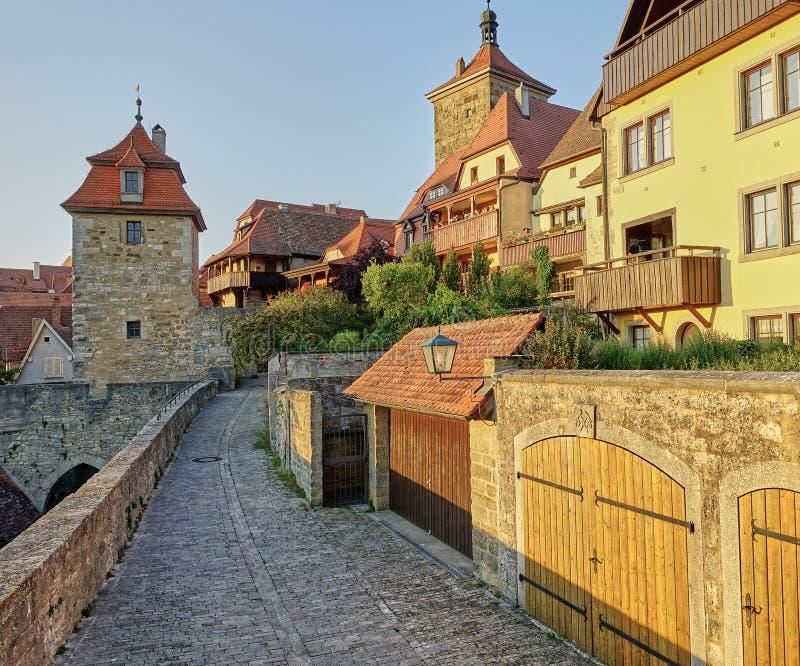 Guld- solnedgång på medeltida byggnader på den romantiska vägen, Tyskland royaltyfri bild