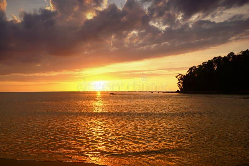 Guld- solnedgång på stranden med mörkt moln och aftonglöd Havsreflexionsröda ljuset som soluppg royaltyfria foton