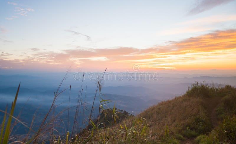 Guld- solnedgångljus med fältet för berg och för blå himmel och gräspå skymning royaltyfri bild