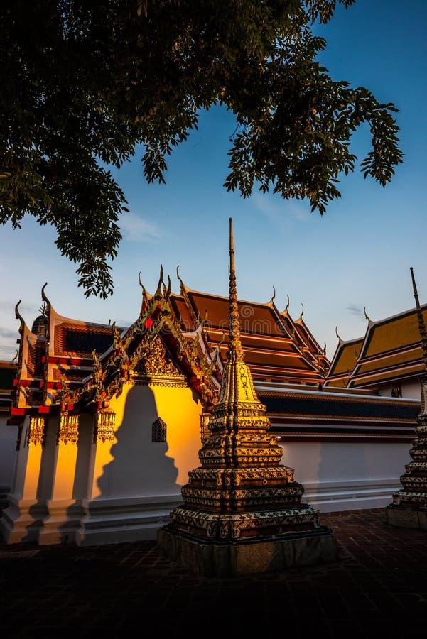 Guld- solnedgångljus på väggarna av Wat Pho Palace Bangkok Thailand Wat Phra Chetuphon Vimolmangklararm Rajwaramahaviharn arkivbild