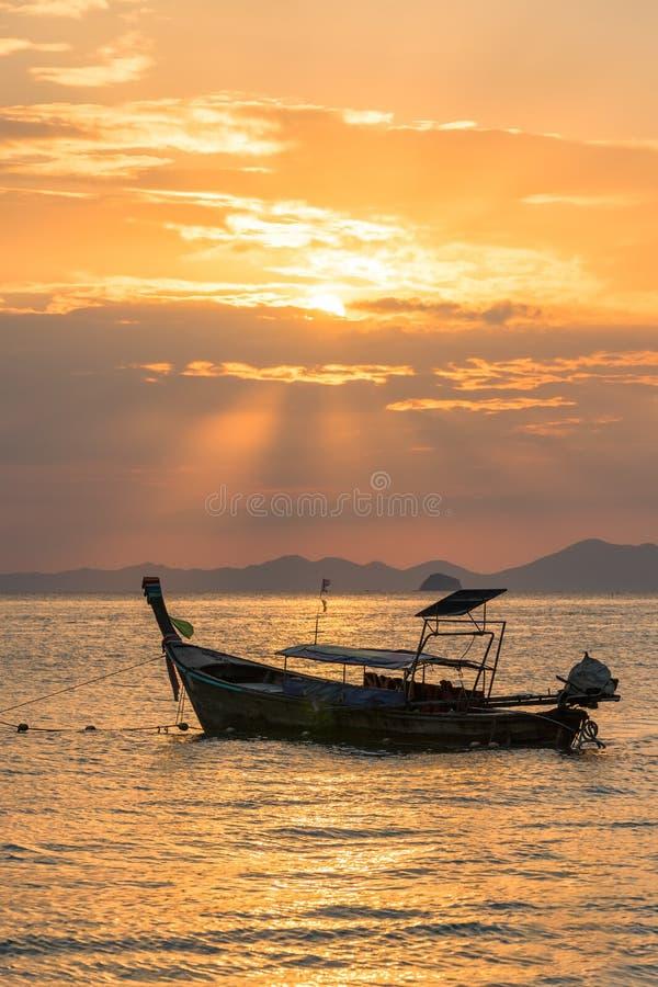 Guld- solstrålar och lokalt tomt thai longtailfartyg under dem i havsvatten på den härliga orange solnedgången royaltyfria foton