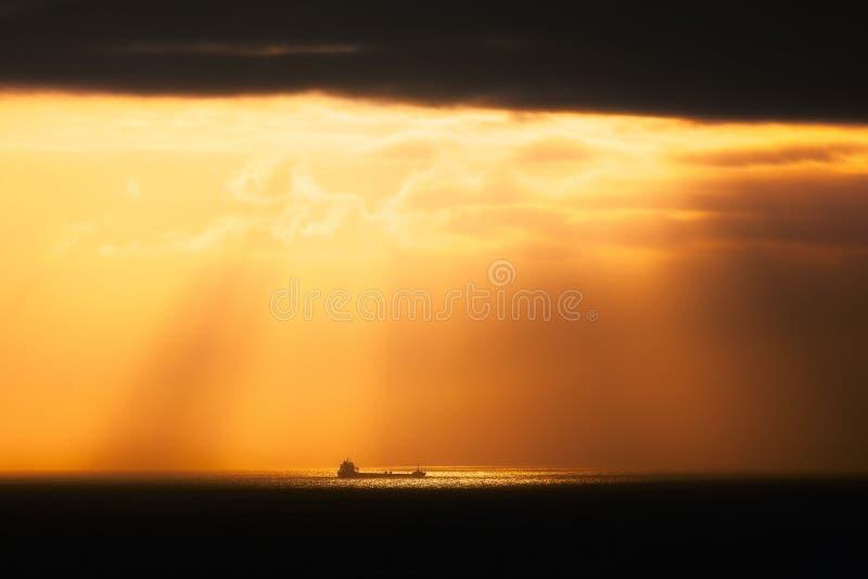 Guld- solstrålar på havet med skeppet royaltyfri fotografi