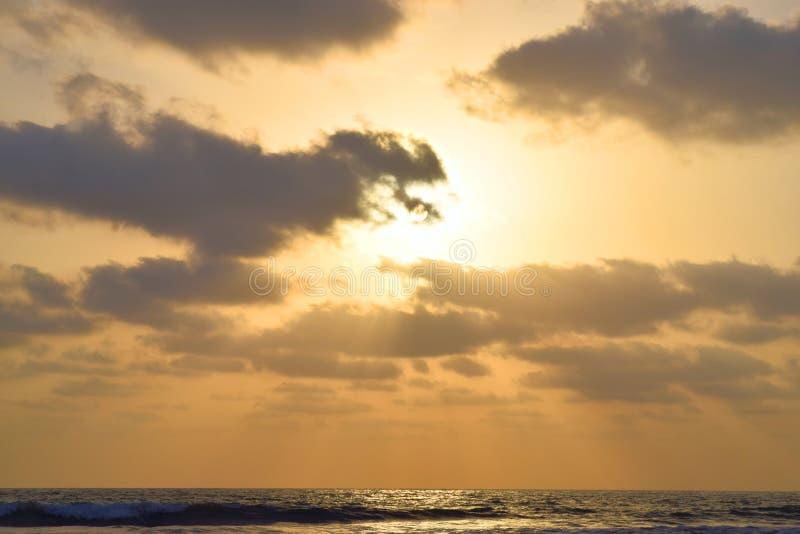 Guld- solstrålar som kommer till och med mörka moln över havet på aftonen arkivbild