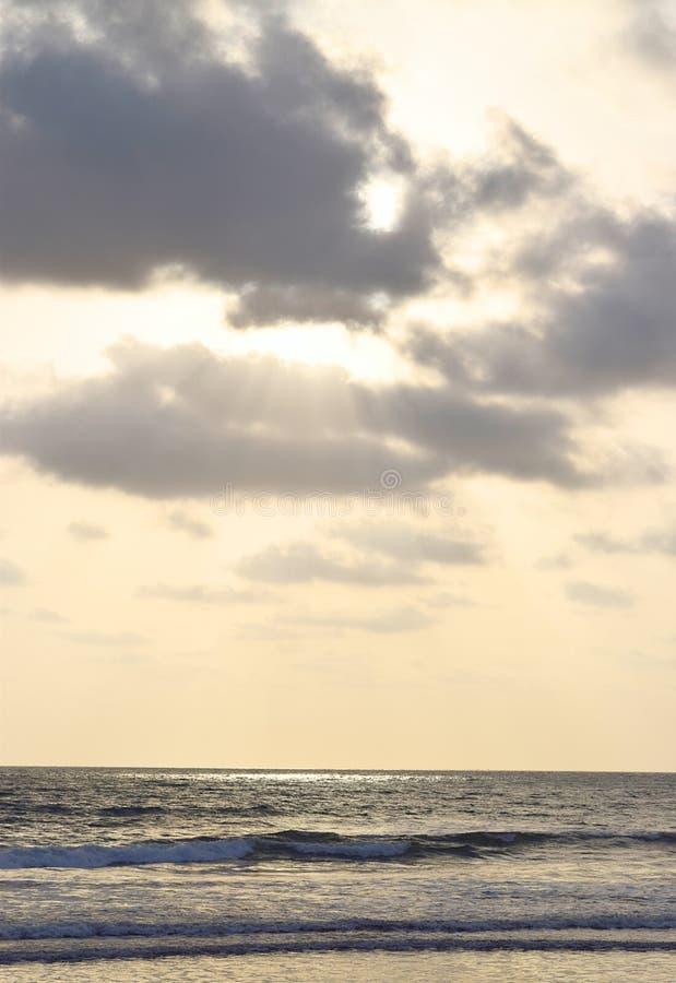 Guld- solstrålar som kommer till och med mörka moln och faller över havet arkivbilder