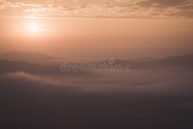 Guld- soluppgång med dimma som lägger i dalen royaltyfri bild