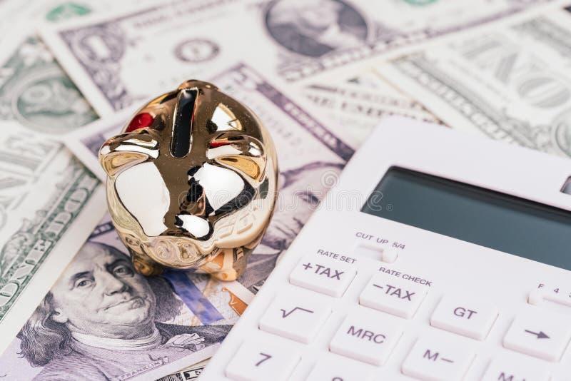 Guld- spargris med den vita räknemaskinen på US dollarsedelpengar, finans, nationalekonomi eller besparing och investeringbegrepp fotografering för bildbyråer