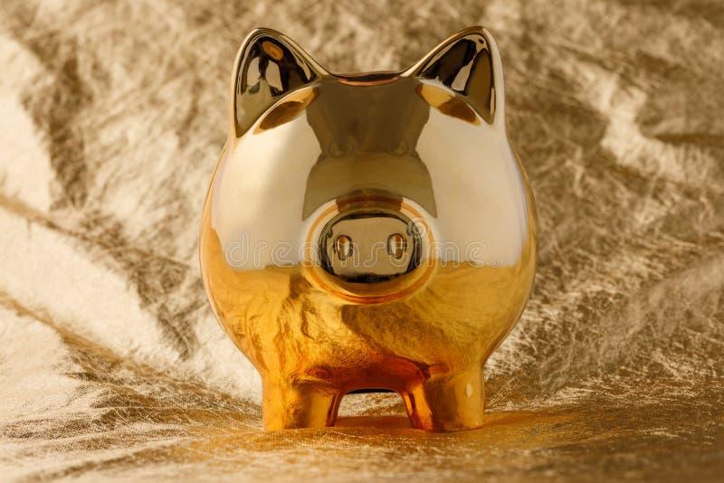 Guld- spargris på en guld- bakgrund Affär och finans royaltyfria bilder