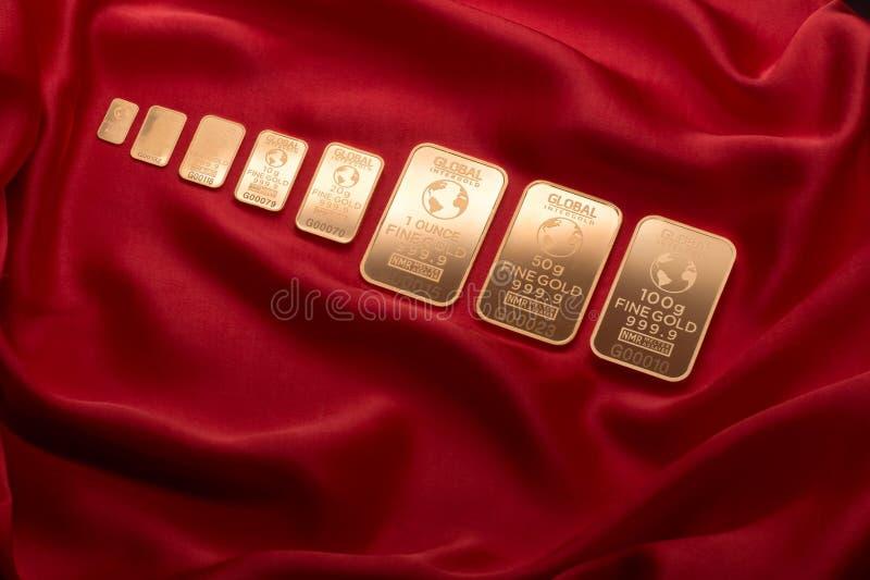 Guld- stänger på röd sammet arkivbilder