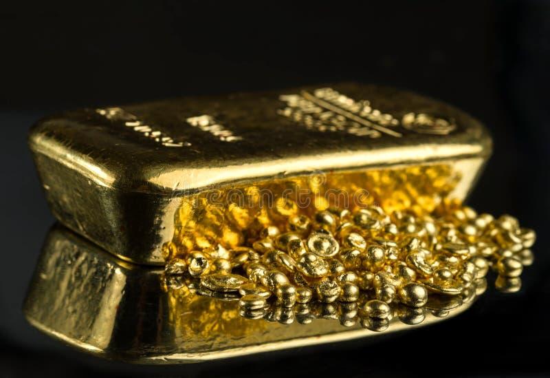 Guld- stång och en hög av rena guld- partiklar på en mörk bakgrund för spegel arkivfoto