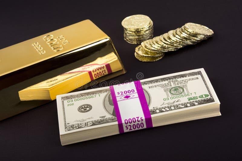 Guld- stång och mynt på svart royaltyfria foton