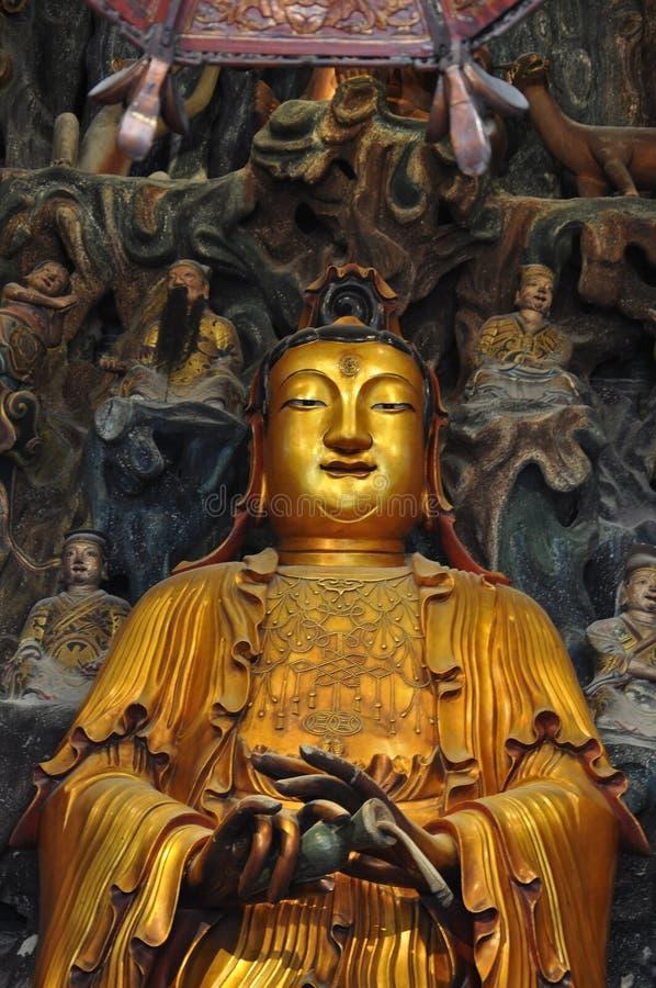 Guld- staty av Guanyin och Sudhana acompanied av deras förlage från den Jade Buddha Temple inre i Shanghai royaltyfri foto