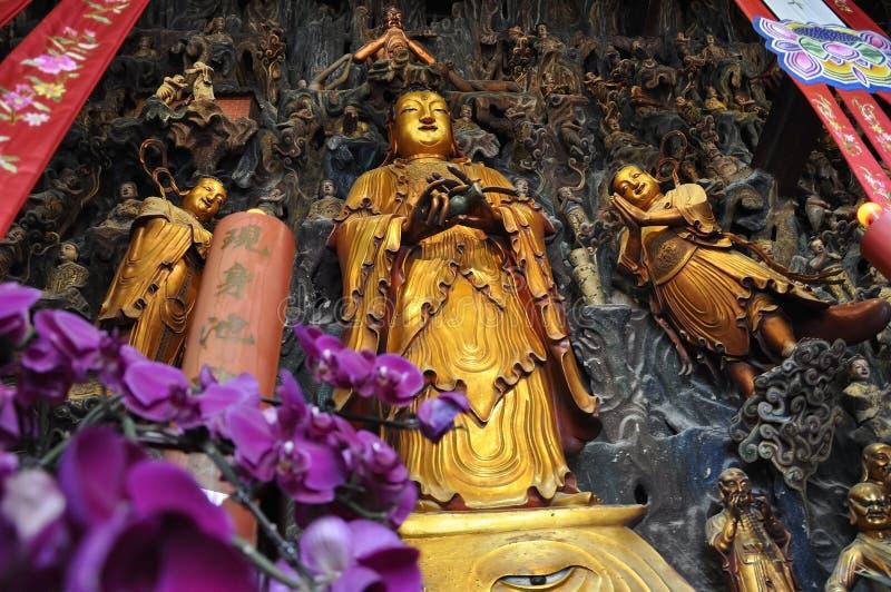 Guld- staty av Guanyin och Sudhana acompanied av deras förlage från den Jade Buddha Temple inre i Shanghai arkivfoto