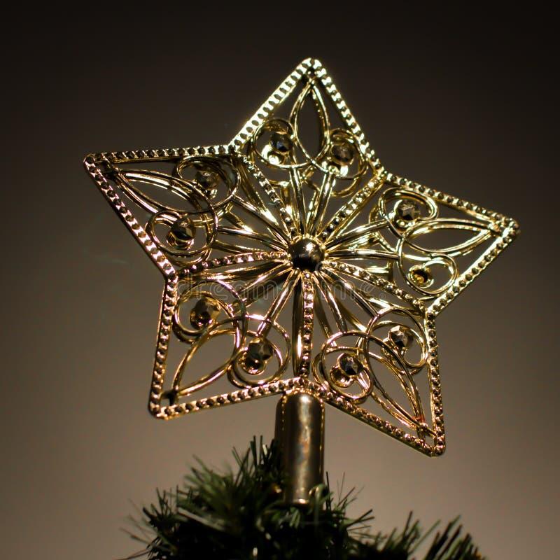 Guld- stjärna överst av julgranen arkivfoto