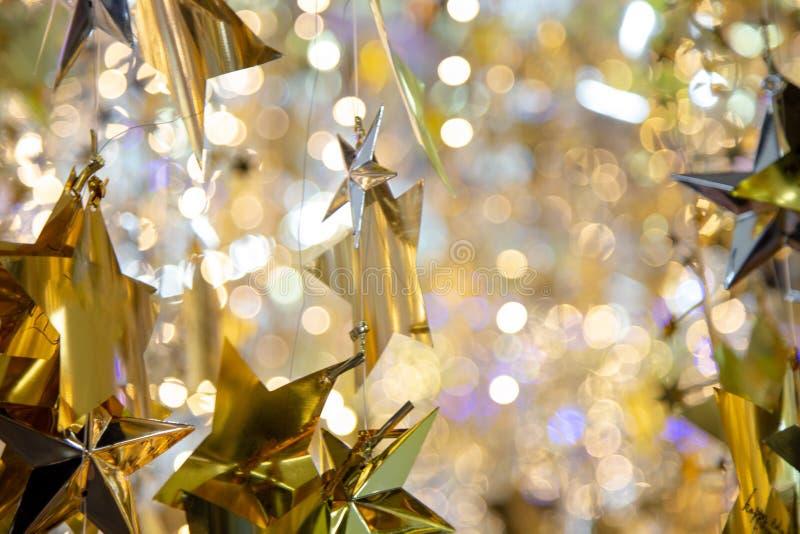 Guld- stjärnajulbakgrund Skinande blänka stjärnor som hänger på magisk suddig bokehbakgrund royaltyfria bilder