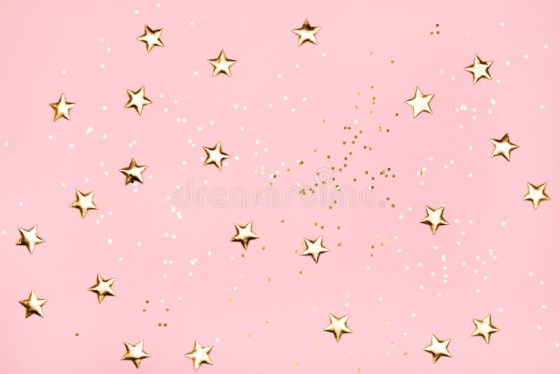 Guld- stjärnor blänker på rosa bakgrund arkivfoton