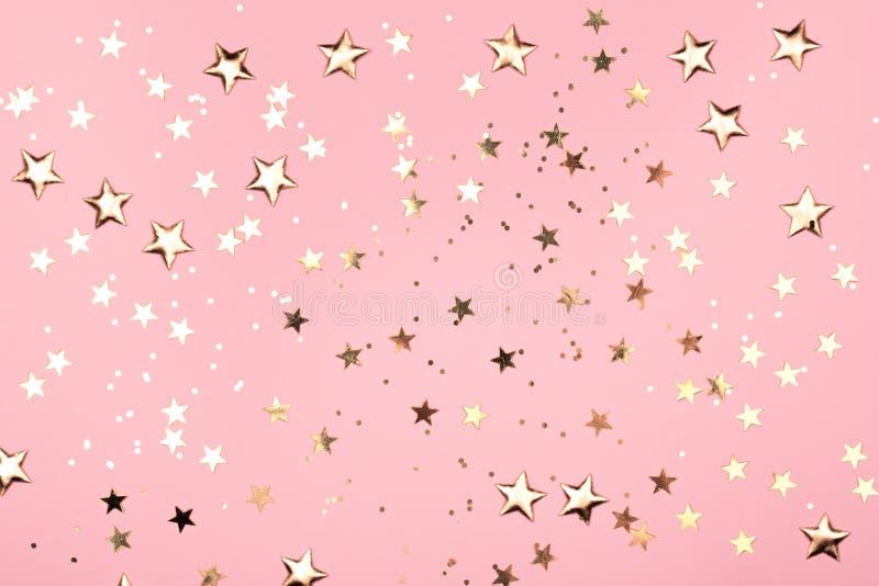 Guld- stjärnor blänker på rosa bakgrund arkivbilder