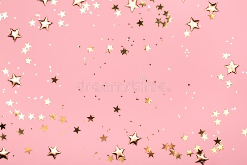 Guld- stj?rnor bl?nker p? rosa bakgrund arkivfoto