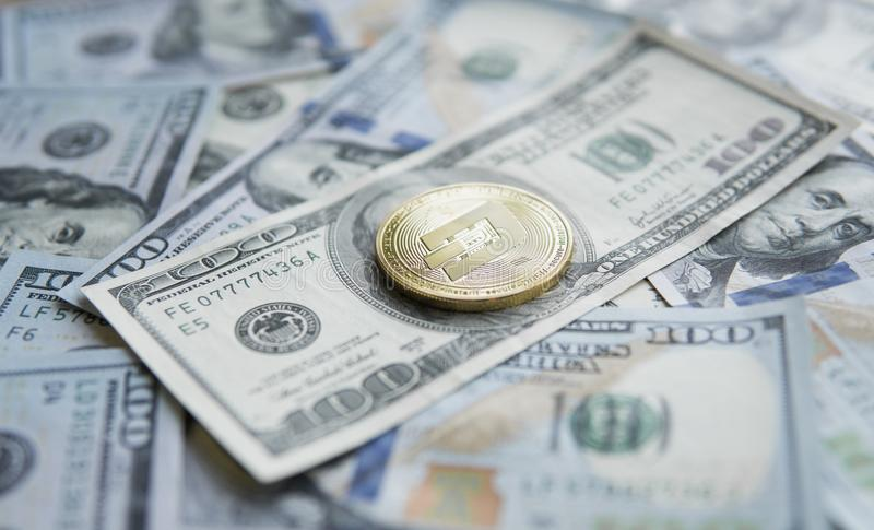 Guld- streckCryptocurrency mynt på en hög av US dollar, kontanta pengar och det crypto valutabegreppet faktiskt Metallmynt av royaltyfri bild